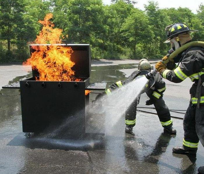 Firefighter putting out a grill fire.
